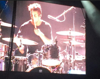 OBB band member playing drums, as seen on the large video screen over the stage