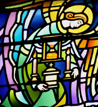 stained glass window of an angel holding symbols of the Anointing of the Sick -- hourglass for the fragility of life, candles for God's presence, oil pot for healing and protection