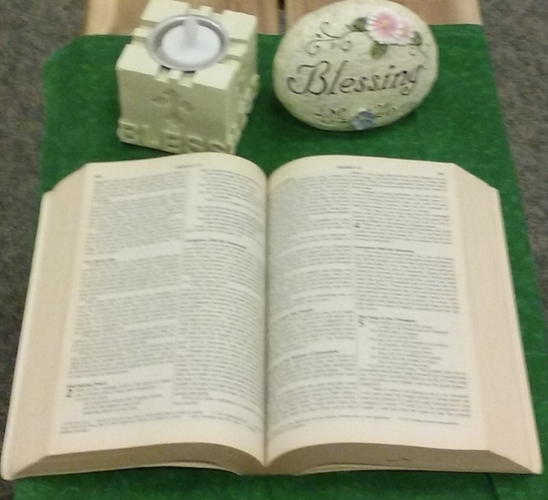 Sacred space in a classroom with a green cloth, Bible, candle and prayer rock